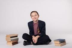 Милый мальчик в костюме сидя на белой предпосылке Куча книг Стоковые Изображения