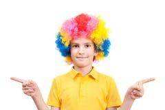Милый мальчик в платье клоуна указывая на стороны Стоковые Изображения RF