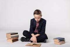 Милый мальчик в усаживании костюма и и чтении книга на белой предпосылке Куча книг Стоковые Фотографии RF