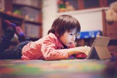 Милый мальчик, лежа на поле в комнате детей, играя на плате Стоковое Изображение