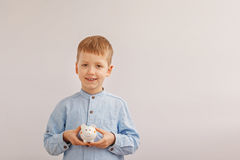 Милый мальчик держа копилку или денежный ящик Ребенок и деньги концепции Стоковое Изображение RF