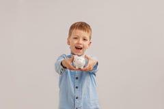 Милый мальчик держа копилку или денежный ящик Ребенок и деньги концепции Стоковое фото RF