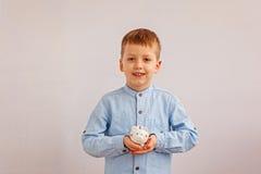 Милый мальчик держа копилку или денежный ящик Стоковые Изображения RF