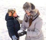 Милый мальчик играя с его матерью в снеге Стоковые Изображения