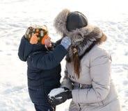 Милый мальчик играя с его матерью в снеге Стоковые Фотографии RF