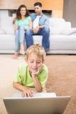Милый мальчик используя компьтер-книжку на половике при родители сидя софа Стоковые Изображения