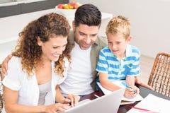 Милый мальчик используя компьтер-книжку с его родителями на таблице Стоковые Фотографии RF
