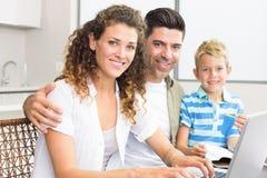 Милый мальчик используя компьтер-книжку с родителями на таблице Стоковая Фотография RF