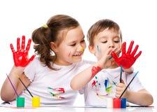 Милый мальчик и девушка играя с красками Стоковые Изображения