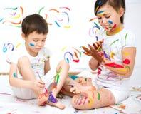Милый мальчик и девушка играя с красками Стоковые Изображения RF