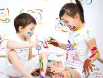 Милый мальчик и девушка играя с красками Стоковое Фото