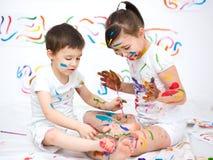 Милый мальчик и девушка играя с красками Стоковые Фотографии RF