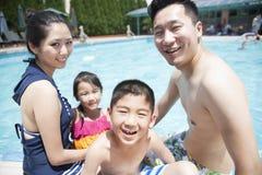 Милый мальчик и его семья играя в бассейне Стоковые Изображения
