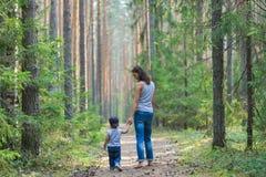Милый мальчик идя в парк держа руку родителей Счастливая семья и концепция образа жизни стоковые фотографии rf