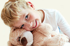 Милый мальчик обнимает его плюшевый медвежонка Стоковые Изображения