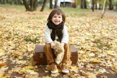 Милый мальчик при медведь игрушки сидя на чемодане в осени стоковое изображение rf