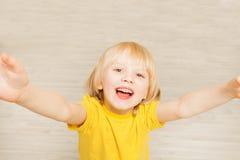 Милый мальчик протягивая руки вверх и смотря камеру Стоковая Фотография