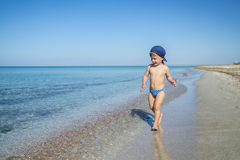 Милый мальчик ребенка бежит в море Стоковые Изображения RF