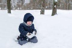 Милый мальчик сидит в снеге в парке в зиме Мальчик очищает снег плиты стоковые изображения