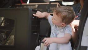 Милый мальчик сидя в автомобиле Семья двигает к новым квартирам, носит вещества на переходе Перестановка к новому дому акции видеоматериалы