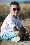 Милый мальчик сидя в поле Стоковая Фотография RF