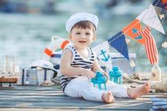 Милый мальчик сидя на поле на пристани внешней, морском стиле. Маленький матрос Стоковое фото RF