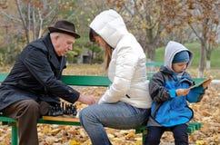 Милый мальчик сидя на скамейке в парке держа планшет пока его мать и дед играют шахмат Стоковые Фото