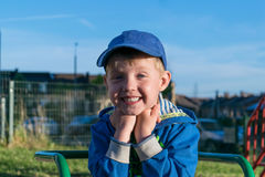 Милый мальчик сидя на спортивной площадке, держа руки около подбородка, улыбки и потеху Стоковое Изображение RF