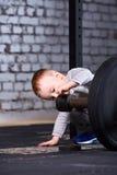 Милый мальчик с гантелями против кирпичной стены в спортзале креста подходящем Стоковые Изображения RF