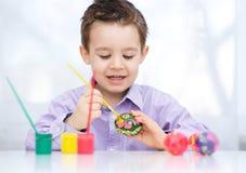 Милый мальчик с корзиной полной красочных яичек Стоковые Фото