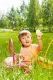 Милый мальчик с кроликом и корзины сидят на траве Стоковое фото RF