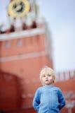 Милый мальчик с покрашенным русским флагом на щеке с башней Россией Spasskaya, Москва на предпосылке, Стоковое фото RF