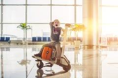 Милый мальчик с померанцовым чемоданом на авиапорте Мальчик на вагонетке и авиапорте Стоковые Изображения RF