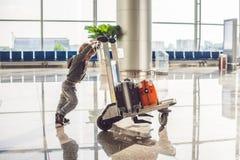 Милый мальчик с померанцовым чемоданом на авиапорте Мальчик на вагонетке и авиапорте Стоковые Фотографии RF