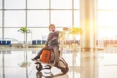 Милый мальчик с померанцовым чемоданом на авиапорте Мальчик на вагонетке и авиапорте Стоковая Фотография