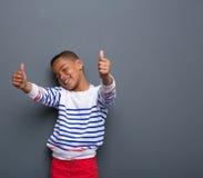 Милый мальчик усмехаясь с большими пальцами руки поднимает знак стоковые изображения