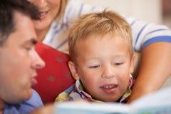 Милый мальчик читая книгу с его родителями стоковые фотографии rf