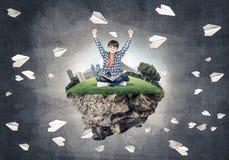 Милый мальчик школьного возраста с книгой исследуя этот большой мир Стоковая Фотография