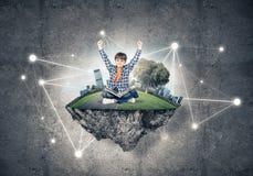 Милый мальчик школьного возраста с книгой исследуя этот большой мир Стоковое Фото