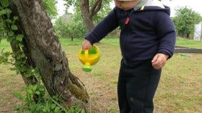Милый мальчик льет большое дерево от малой моча чонсервной банкы Ребенк в голубом велосипеде и белая шляпа в ` родителей садовнич сток-видео