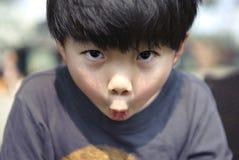 Милый мальчик для того чтобы сделать преувеличенные выражения лица Стоковое Изображение