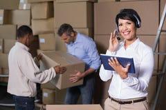 Милый менеджер склада используя таблетку во время периода занятости Стоковые Изображения