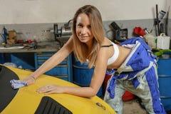 Милый механик девушки полирует клобук автомобиля Стоковое Изображение RF