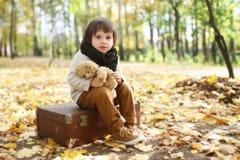 Милый модно одетый мальчик сидя на чемодане в осени p стоковые фото
