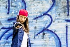 Милый молодой белокурый подросток девушки в рубашке бейсбольной кепки и джинсовой ткани на предпосылке каменной стены Стоковая Фотография