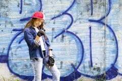 Милый молодой белокурый подросток девушки в рубашке бейсбольной кепки и джинсовой ткани на предпосылке каменной стены Стоковое фото RF