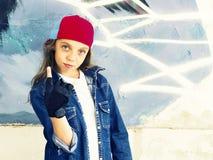 Милый молодой белокурый подросток девушки в рубашке бейсбольной кепки и джинсовой ткани на предпосылке каменной стены Стоковое Изображение RF