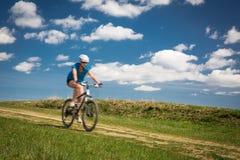 Милый, молодой женский велосипедист outdoors на ее горном велосипеде Стоковое Фото