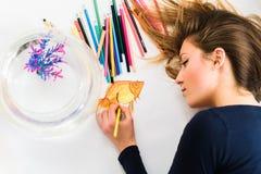Милый молодой женский художник делает изображение поднимающего вверх маленьких золотых рыб близкое Взгляд сверху Стоковые Изображения RF