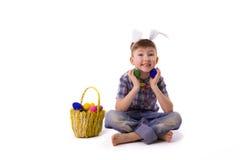 Милый молодой мальчик в изображении зайчика пасхи с яичками Стоковое фото RF